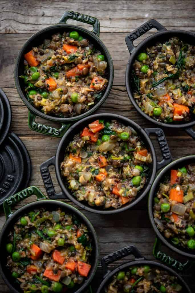 Overhead of vegan lentil shepherd's pie in mini Staub cocottes