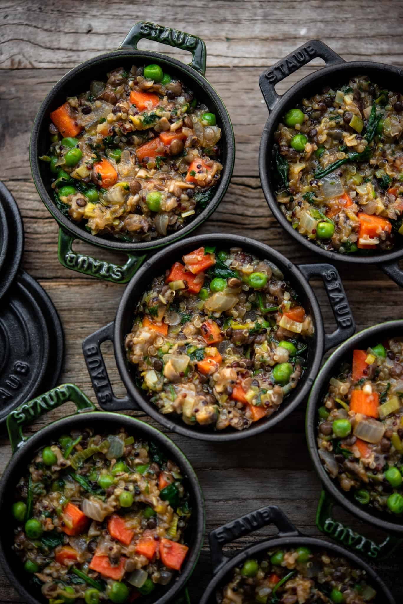 Overhead of vegan lentil shepherd's pie in mini Staub cocottes