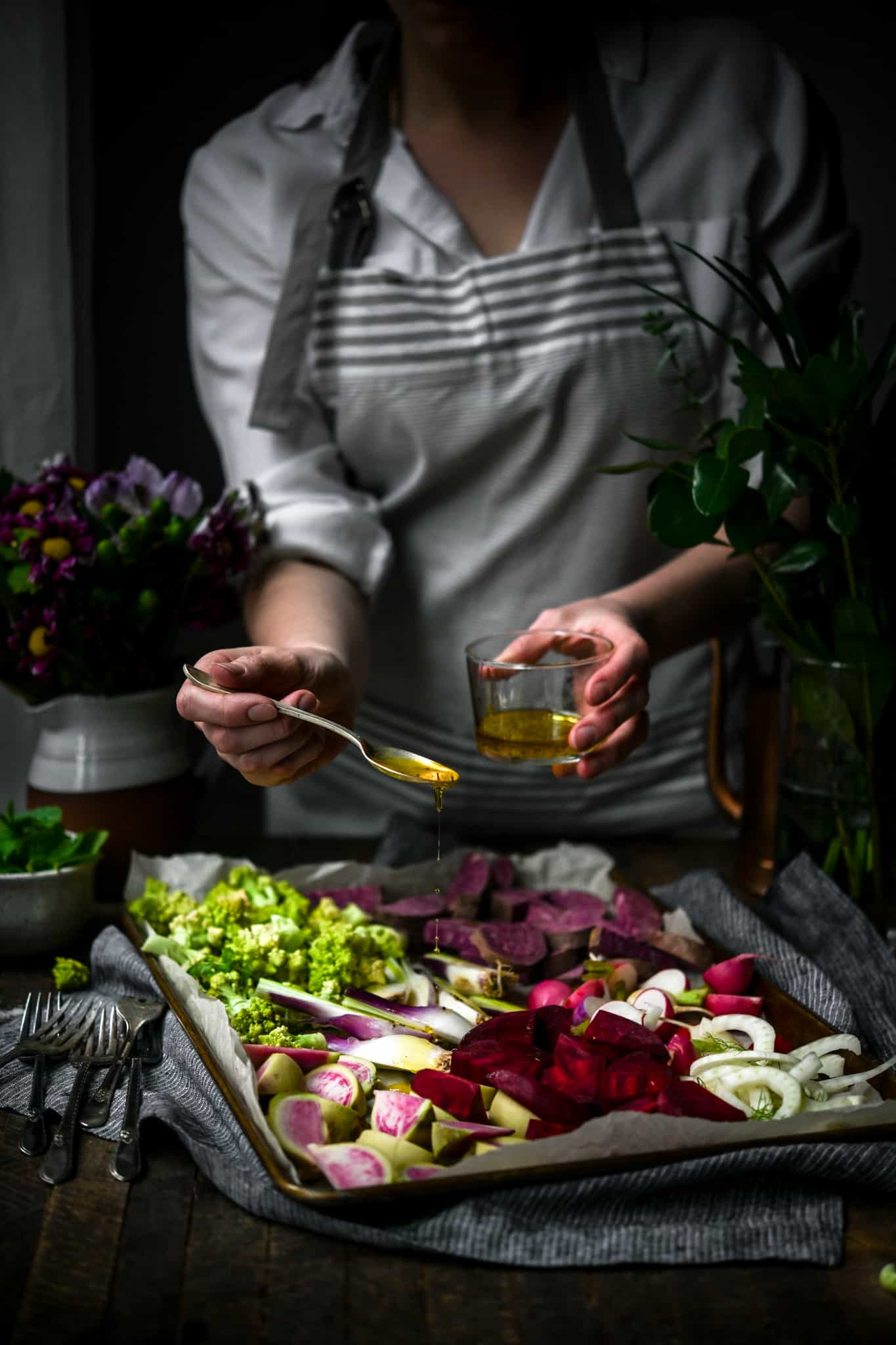 Person in apron drizzling olive oil onto sheet pan filled with vegetables