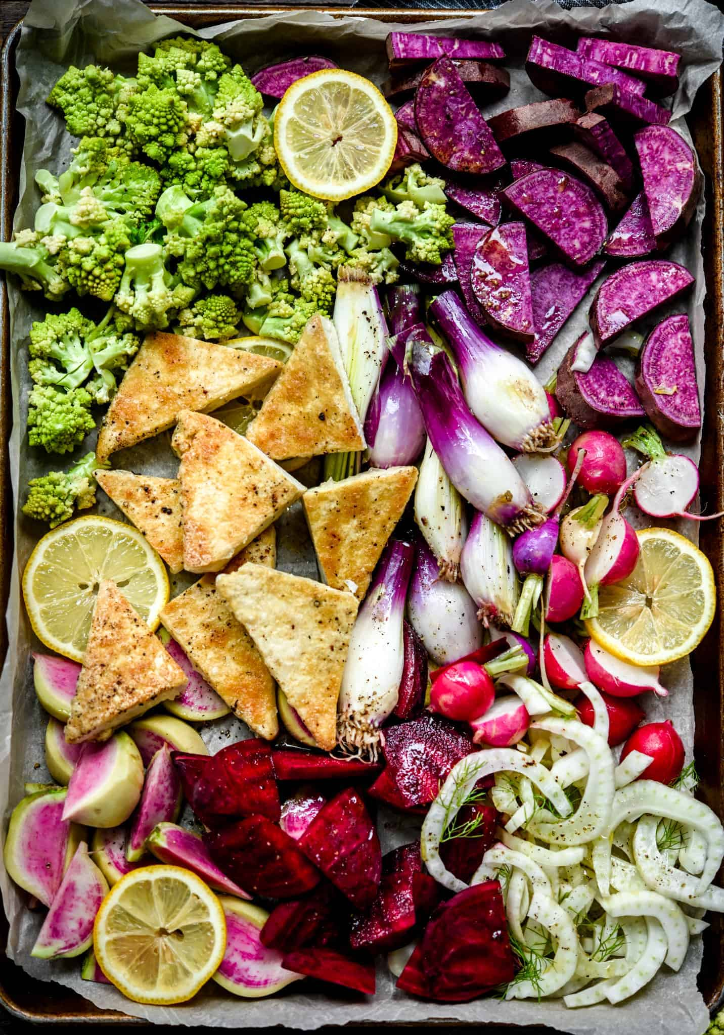 Overhead of sheet pan with uncooked purple, pink and green vegetables and tofu