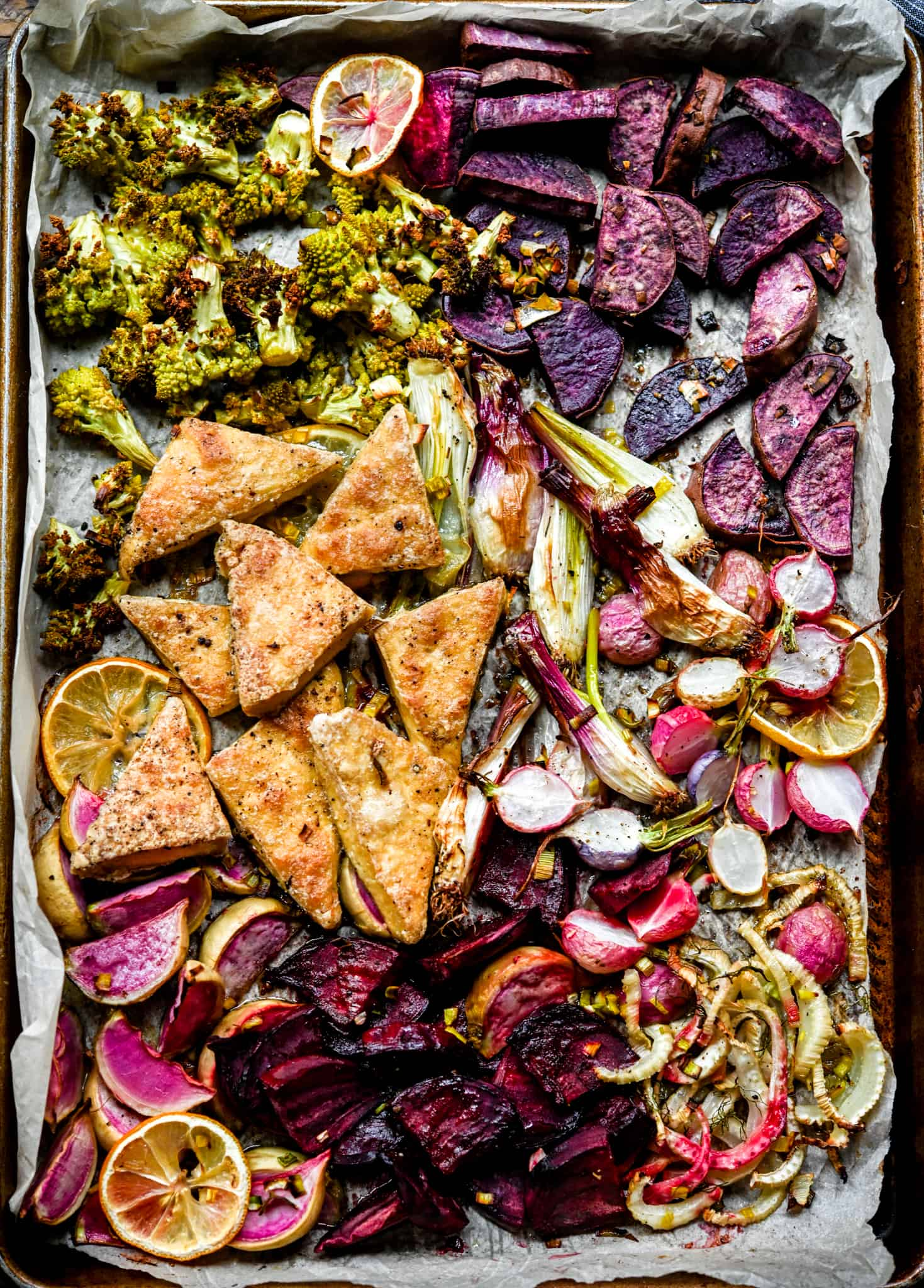Overhead of sheet pan with purple, pink and green vegetables and tofu