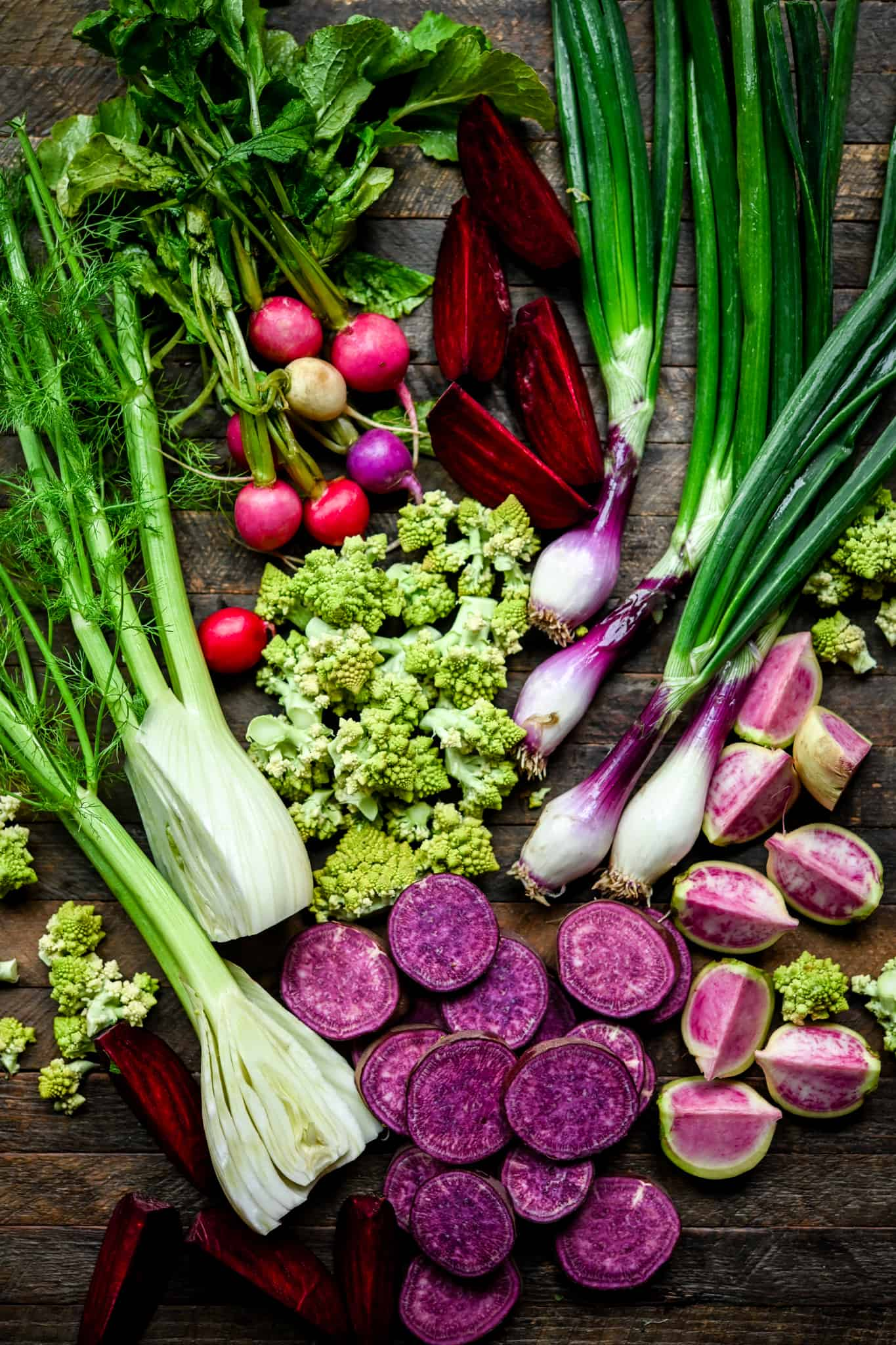 Overhead view of raw purple, green, pink and red vegetables on wood background