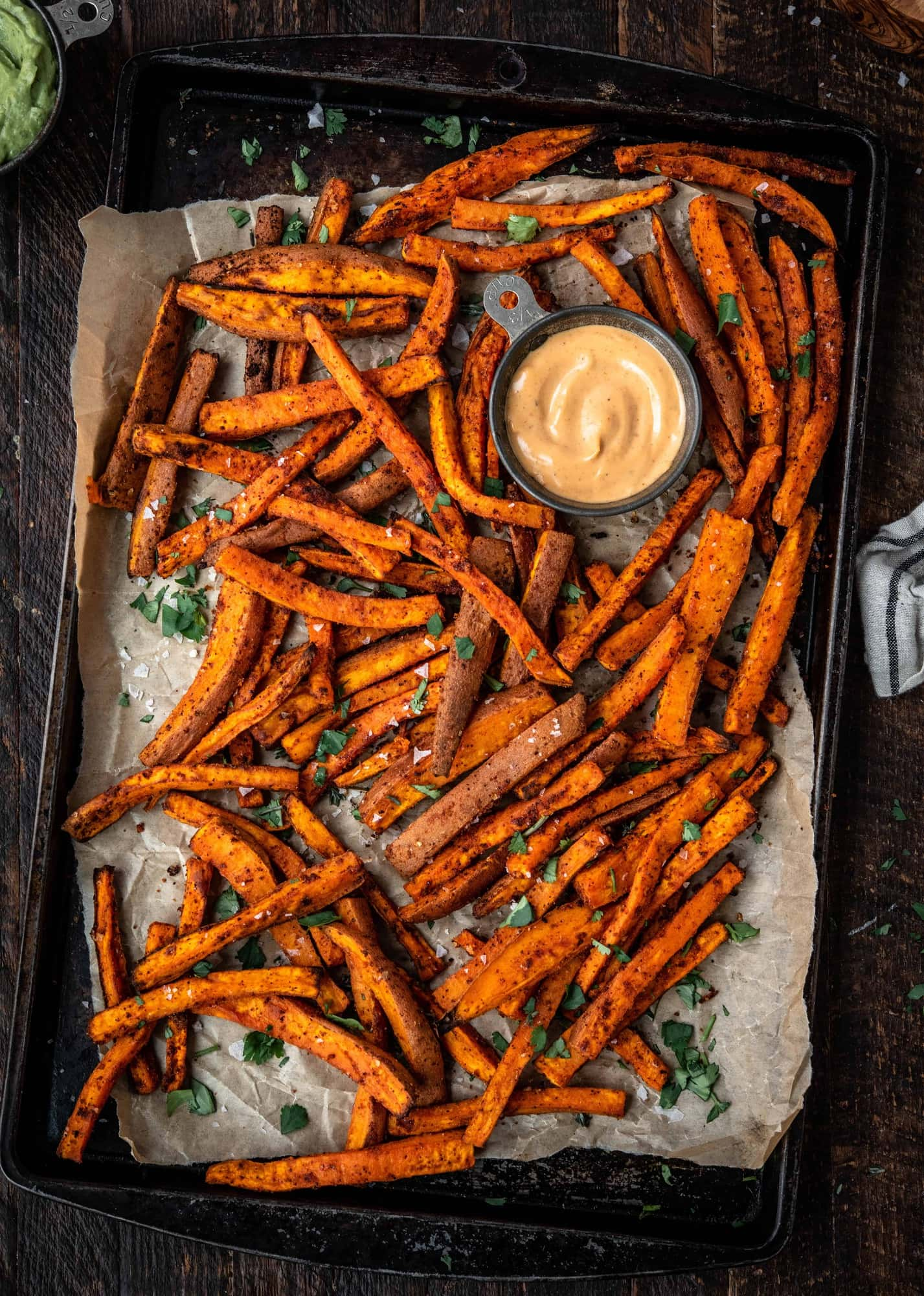Overhead of spiced sweet potato fries on an antique baking sheet with fresh herbs and aioli