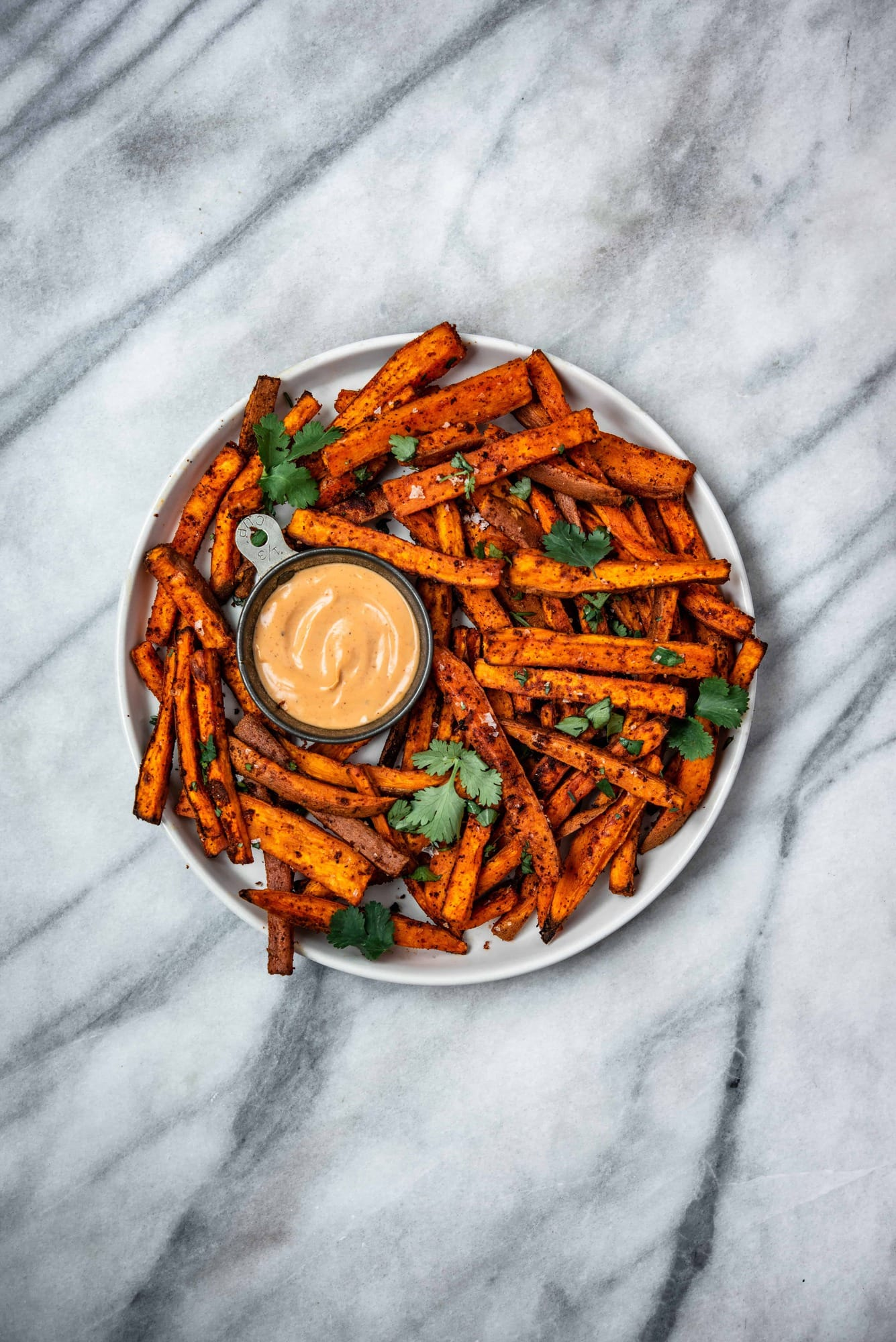 Overhead of spiced sweet potato fries on a white plate with fresh herbs and aioli on a marble background