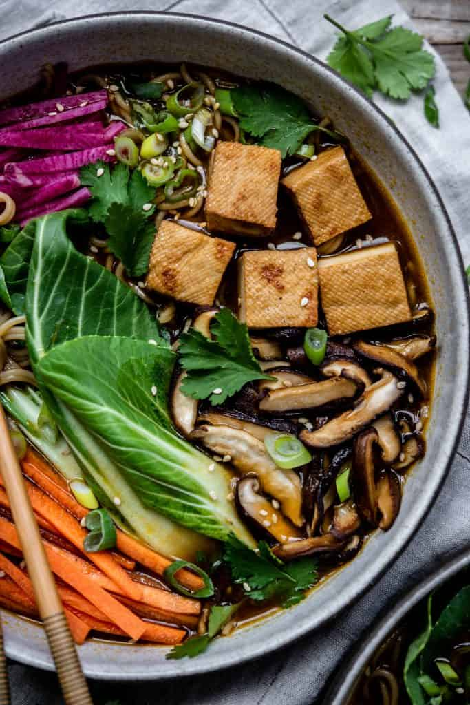 Close up of homemade vegan ramen in a white bowl with chopsticks, bok choy, tofu, mushrooms, carrots and noodles