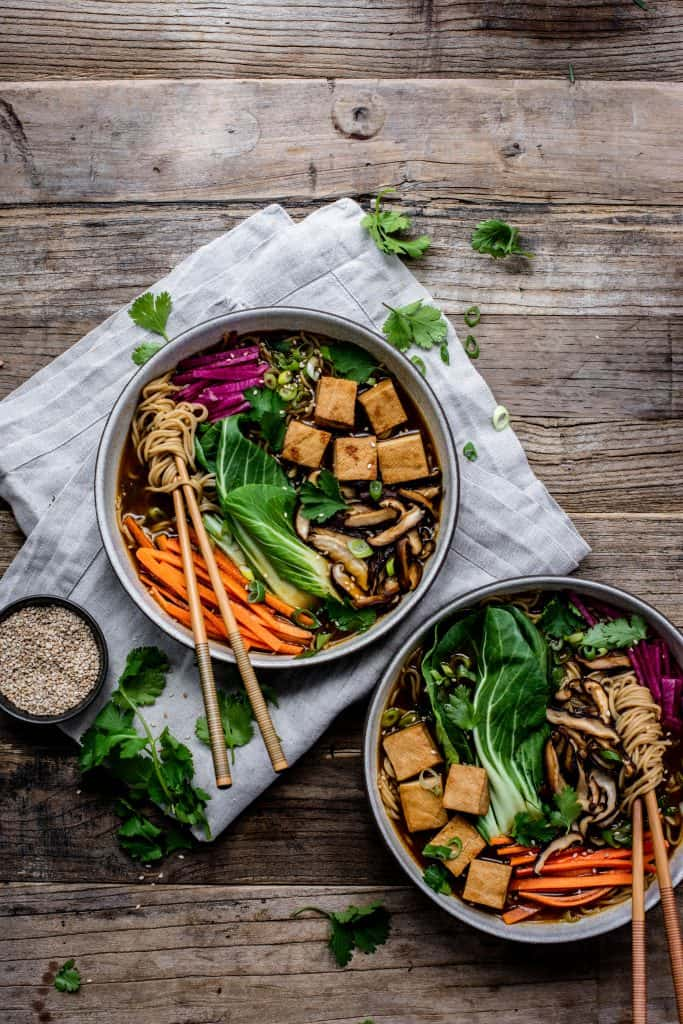 Overhead view of homemade vegan ramen in a white bowl with chopsticks, bok choy, tofu, mushrooms, carrots and noodles