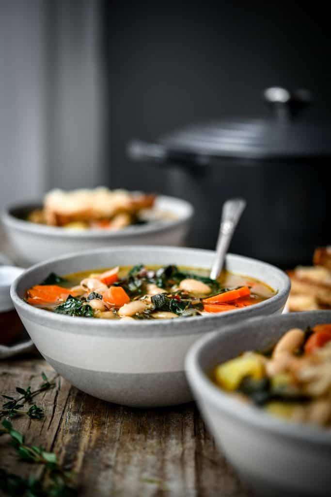 Side view of white bean kale soup in a grey bowl on a wood table