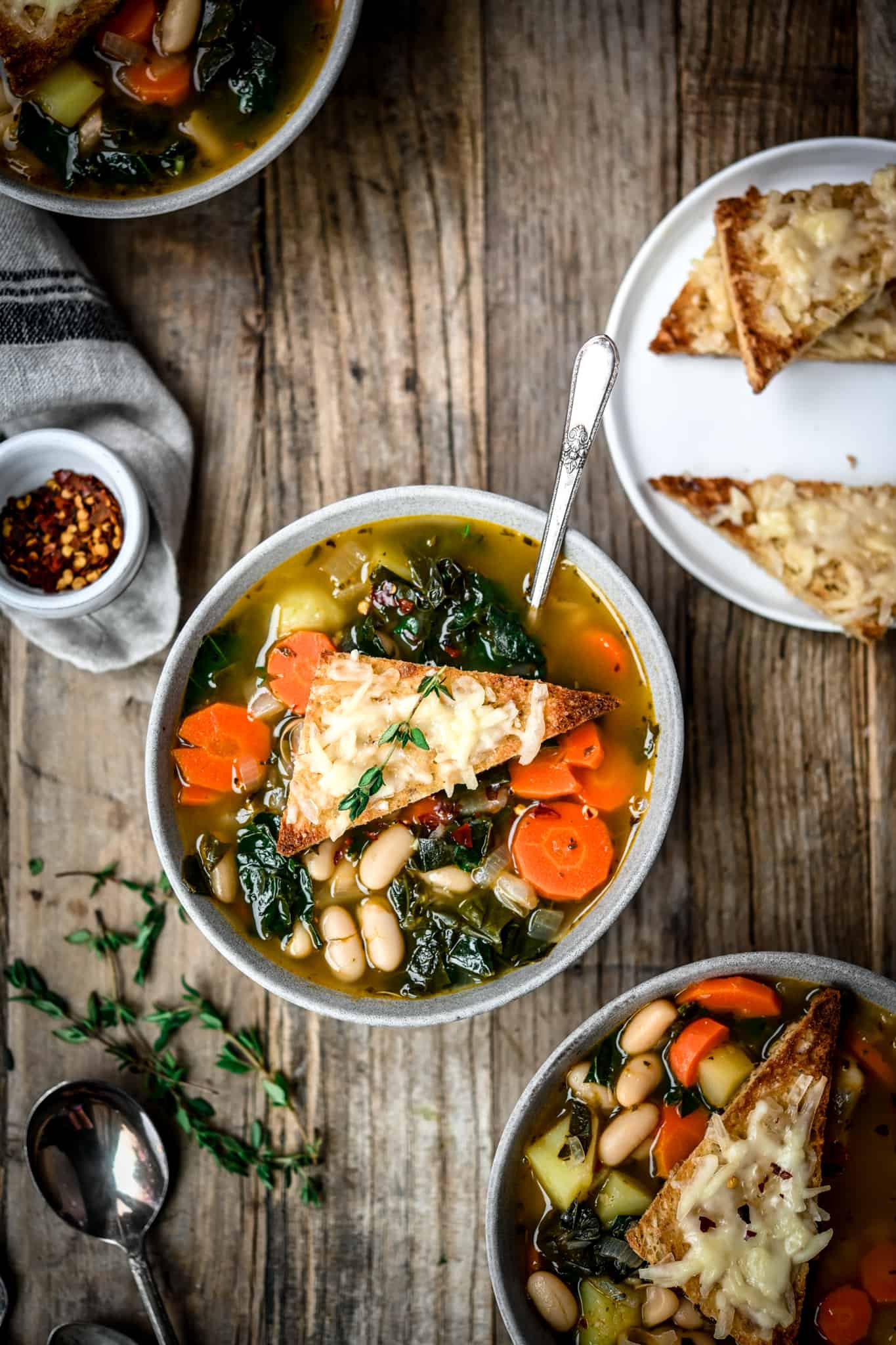 Overhead view of white bean kale soup in a grey bowl on a wood table