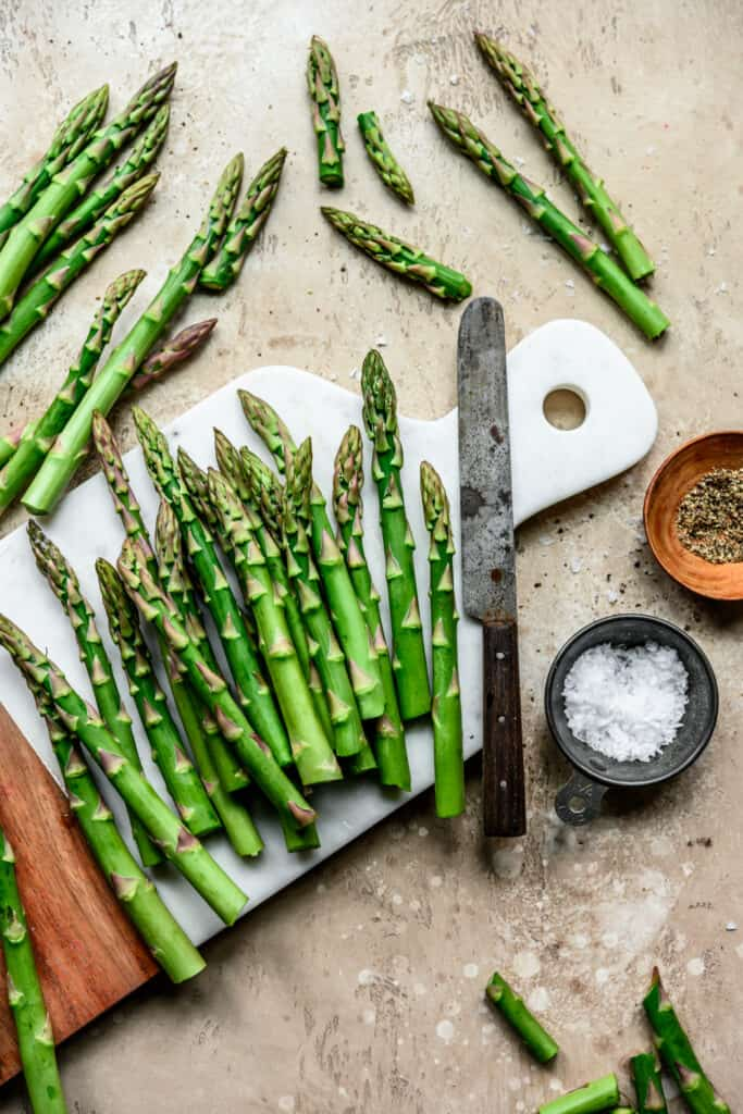 Overhead view of beautiful food photography of asparagus spears on a white marble cutting board on a light tan background