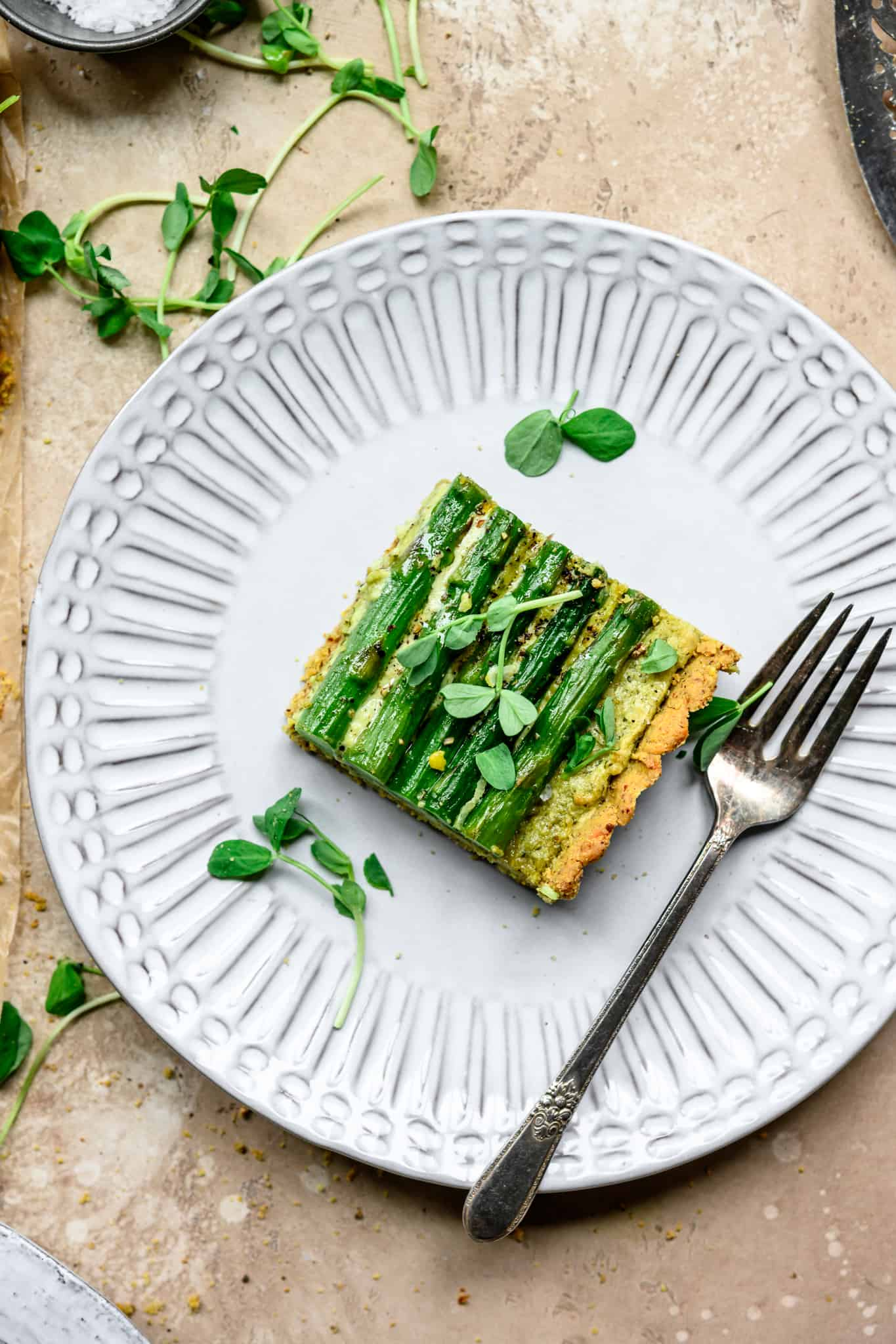 Overhead view of slice of vegan ricotta and asparagus tart on a white plate with fork