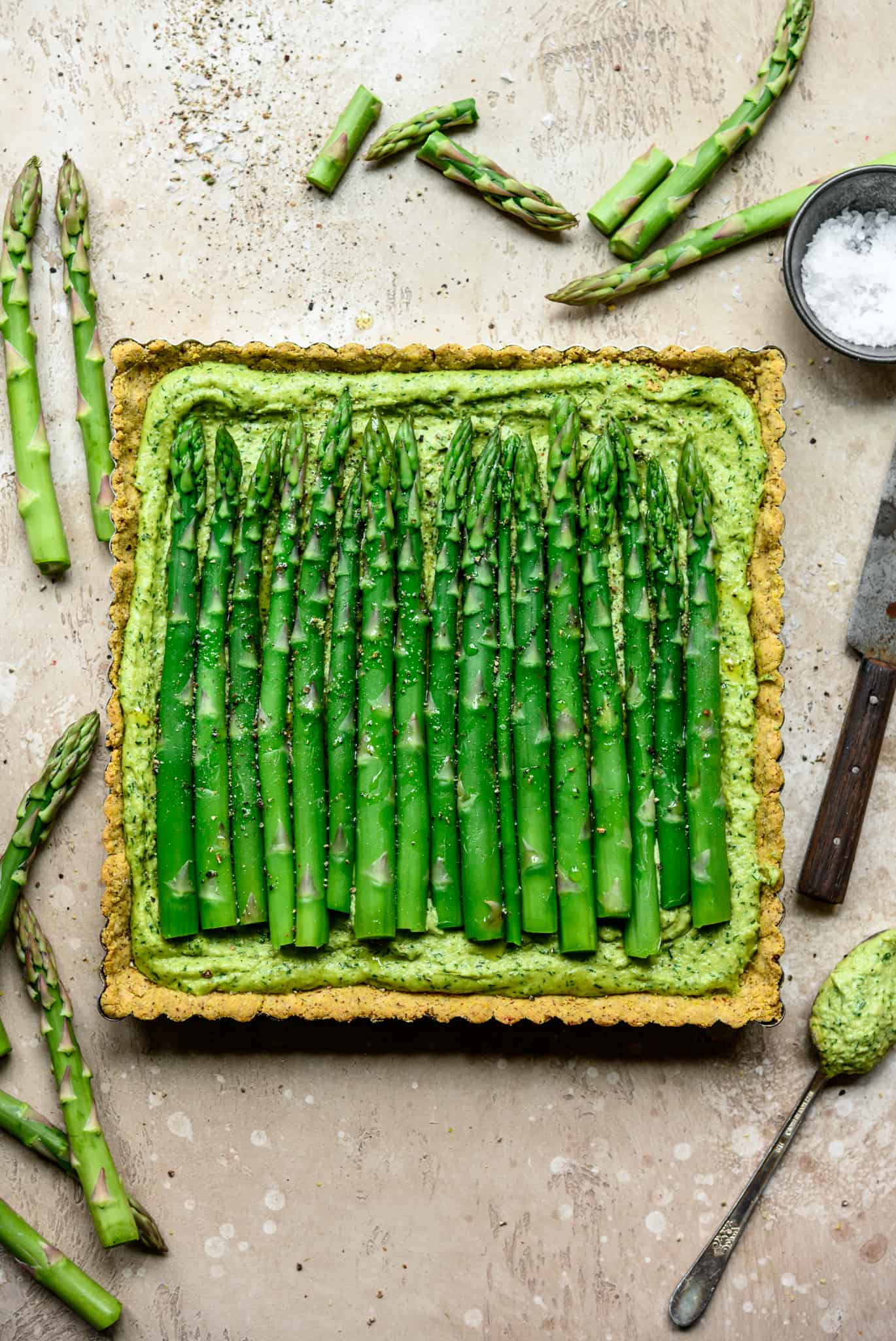Overhead view of vegan ricotta and asparagus tart with a cornmeal crust on light tan background