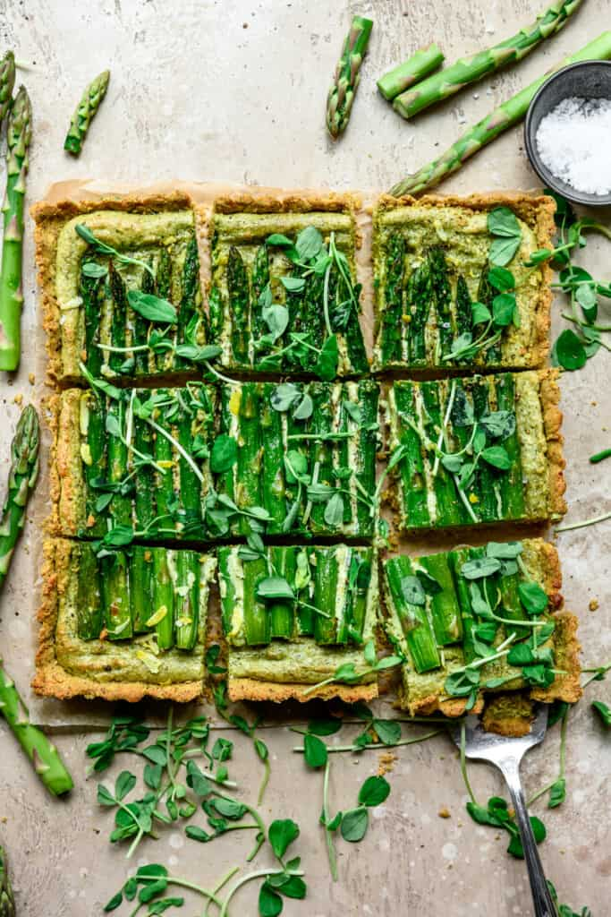 Overhead view of vegan ricotta and asparagus tart with a cornmeal crust sliced into squares on light tan background