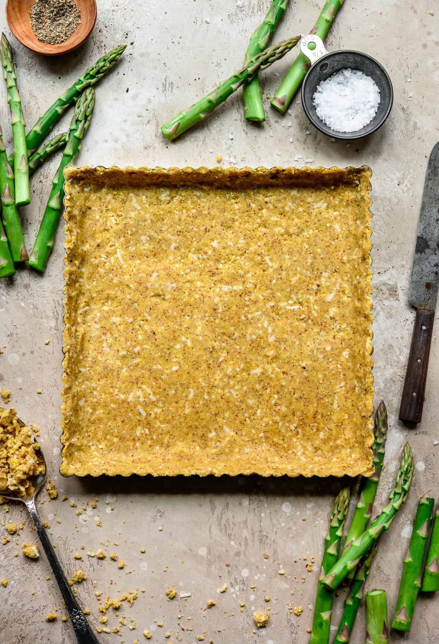 Overhead view of cornmeal crust pressed into square tart pan on light tan background