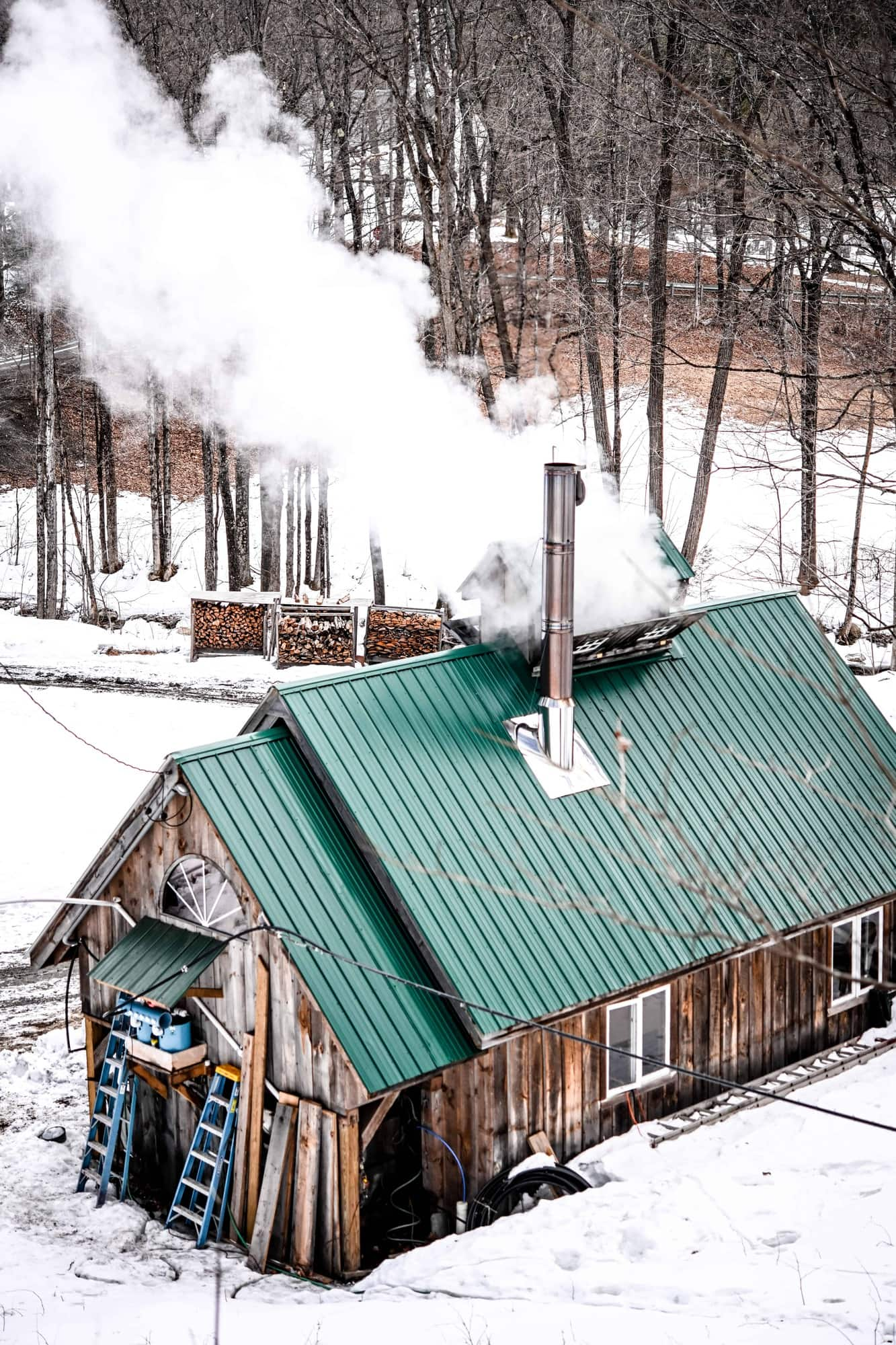 Back view of a Vermont Sugarhouse with steam coming from roof in winter