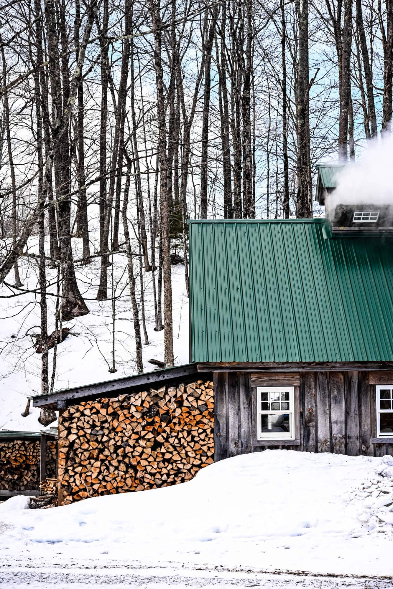 Side view of a Vermont Sugarhouse in winter with stack of wood and steam coming out of top of house