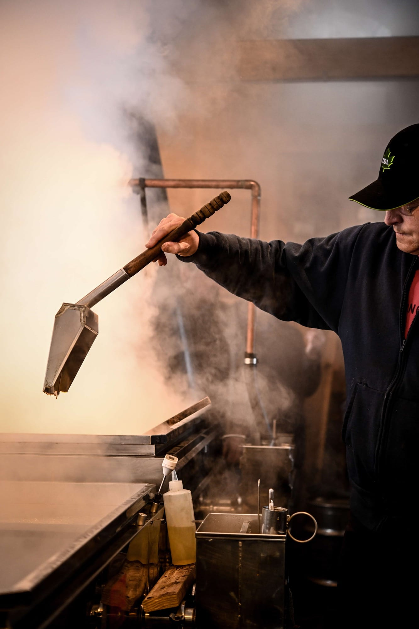 Man in maple sugarhouse testing viscosity of maple syrup