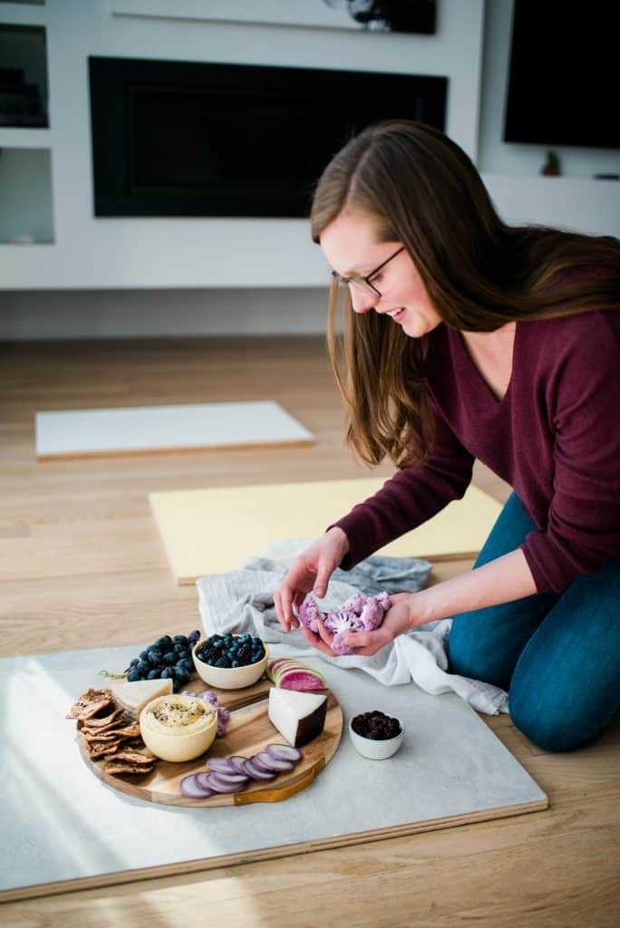 Photographer styling a snack platter for photo