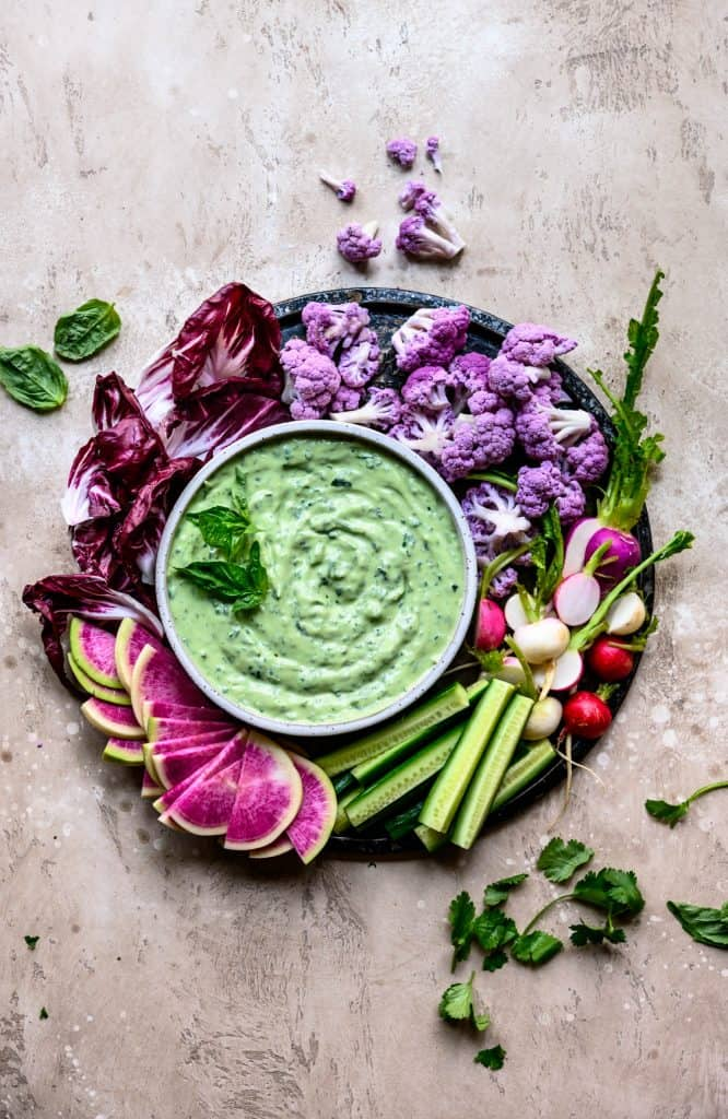 Overhead of herby whipped tofu dip with fresh colorful vegetables on a round platter