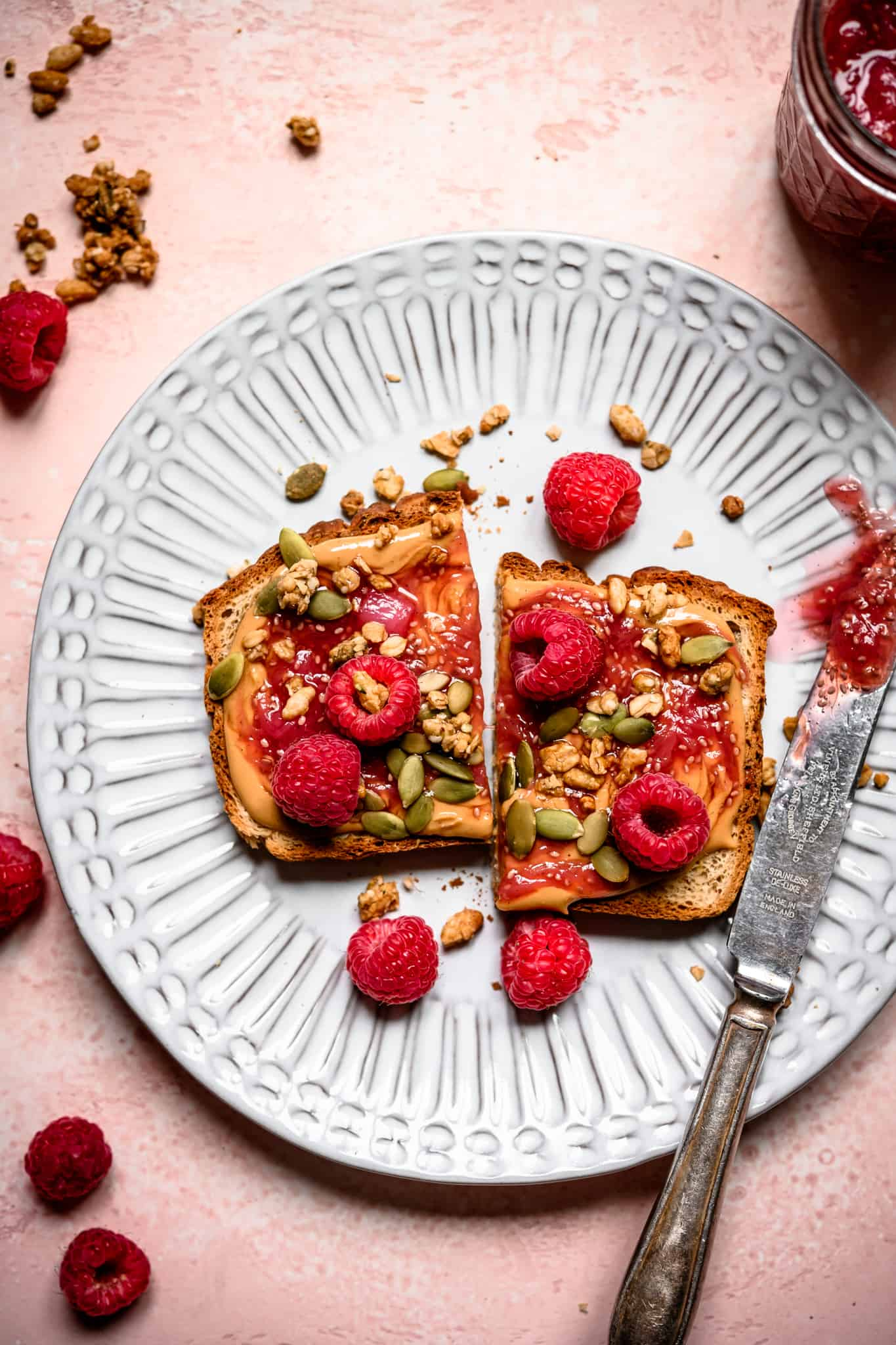 Overhead view of peanut butter and rhubarb compote toast on a white plate with fresh raspberries
