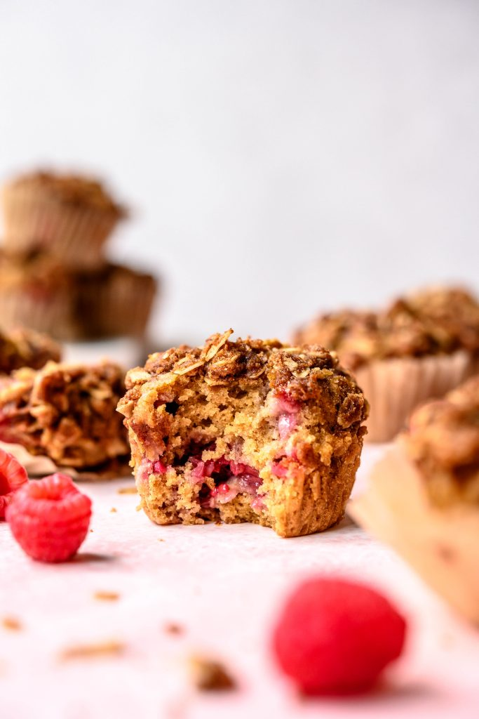 Side view of vegan raspberry rhubarb muffins with bite taken out on pink background