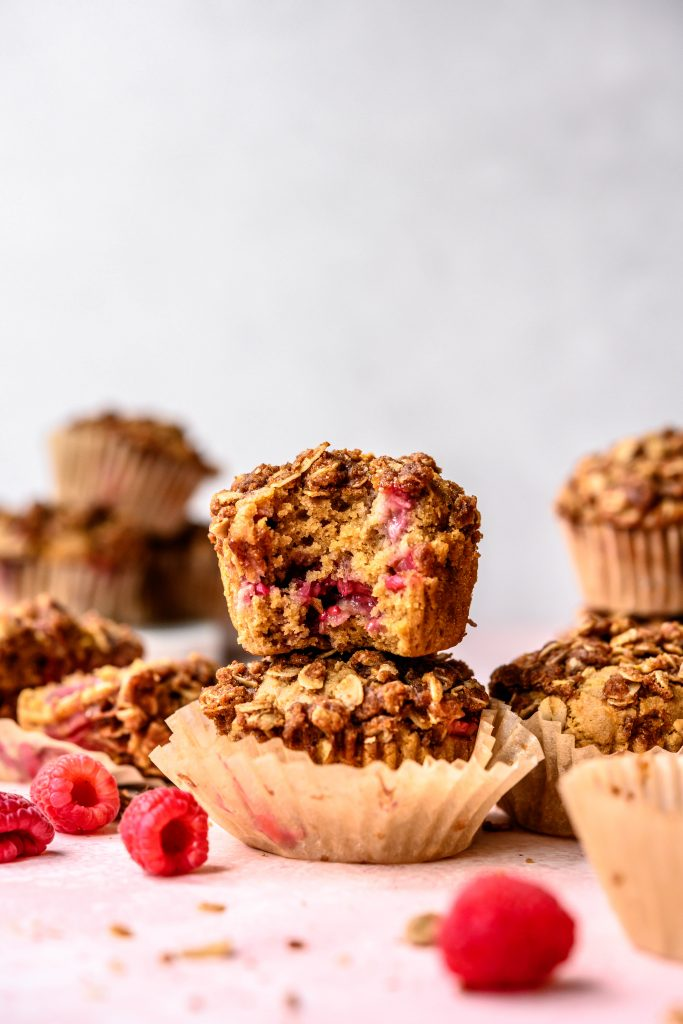 Side view of stacked vegan raspberry rhubarb muffins on pink background