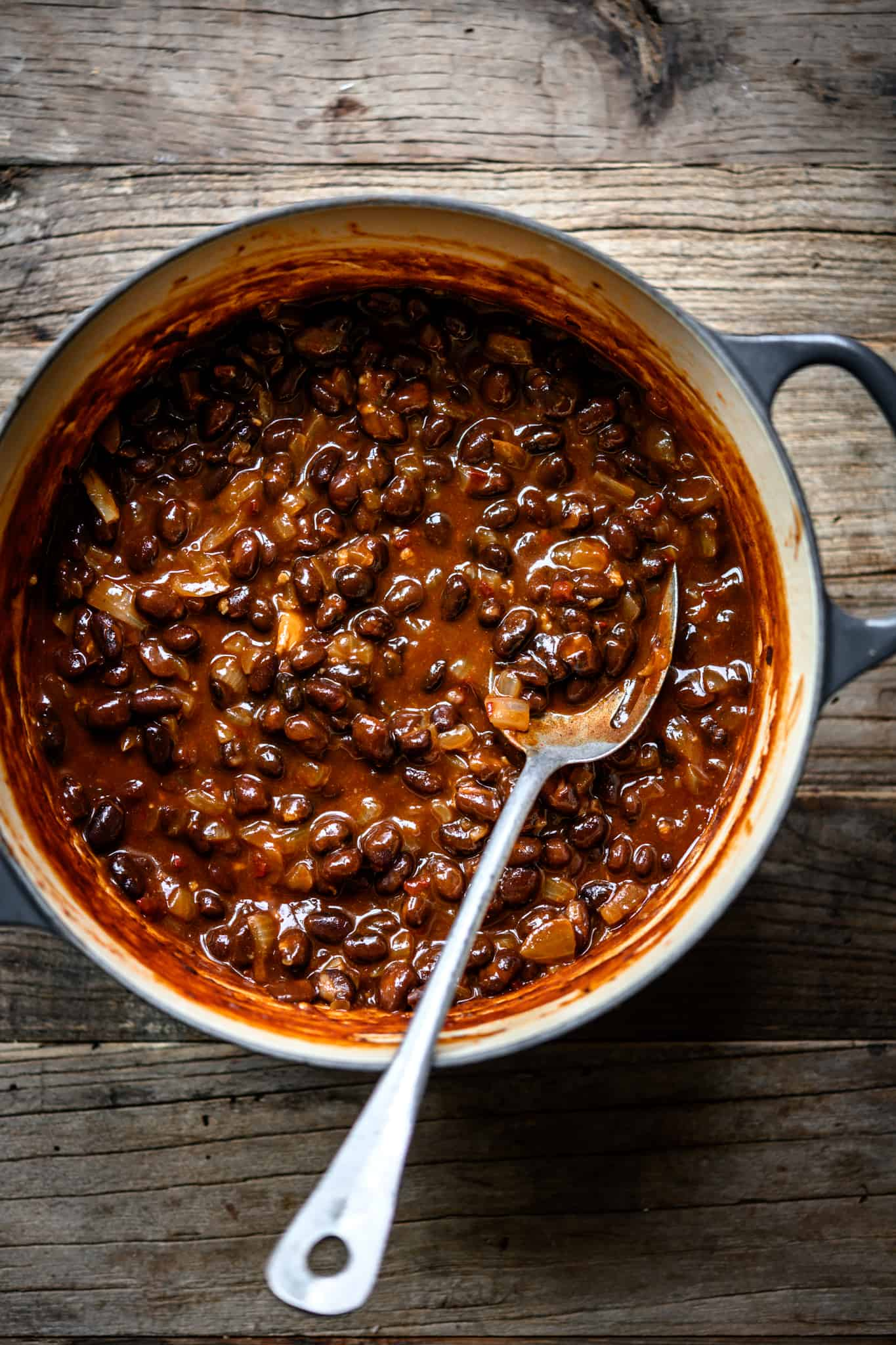 Overhead view of spicy vegan black beans in a large pot