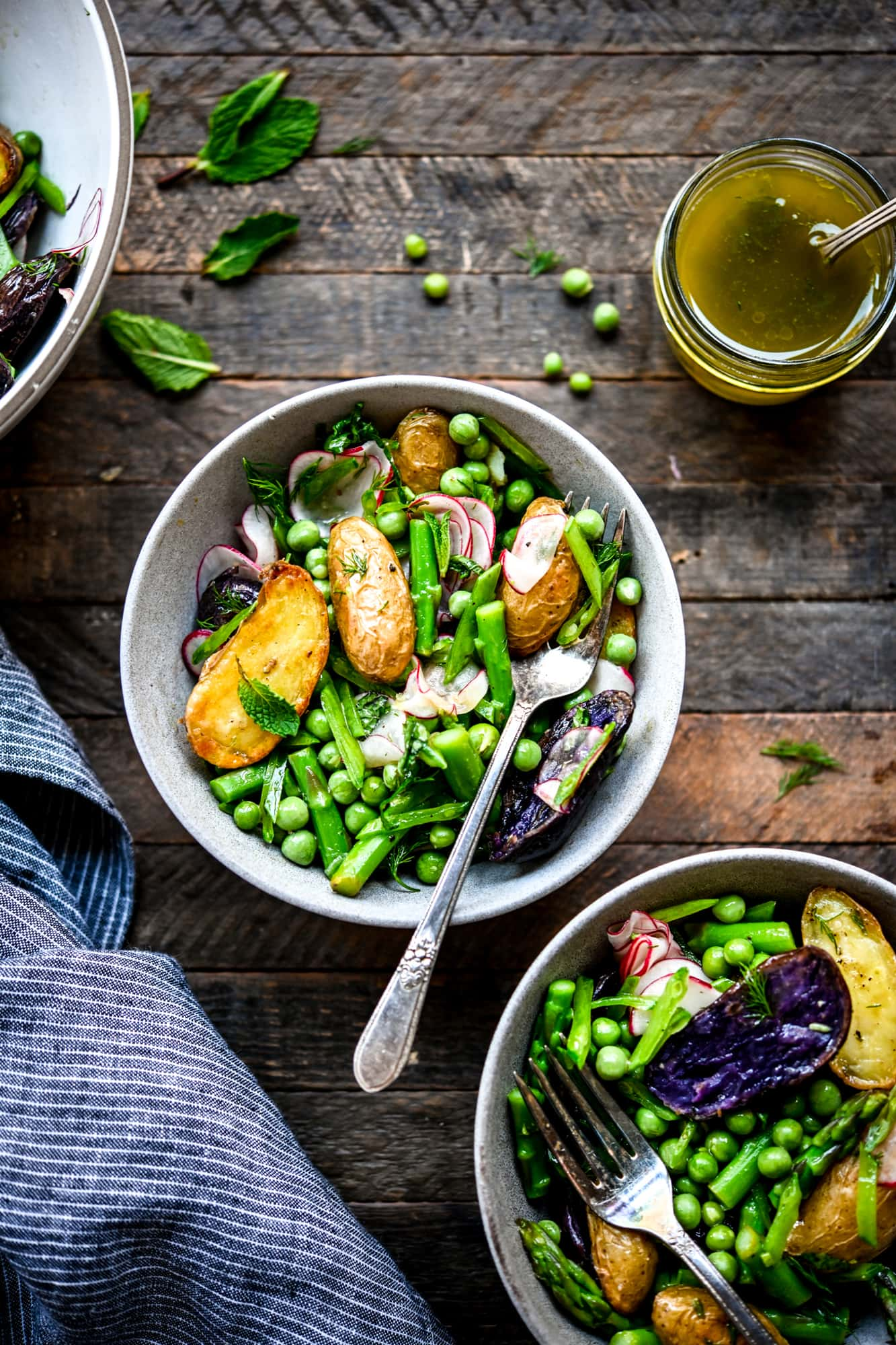 Overhead view of two bowls of spring potato salad on wood background