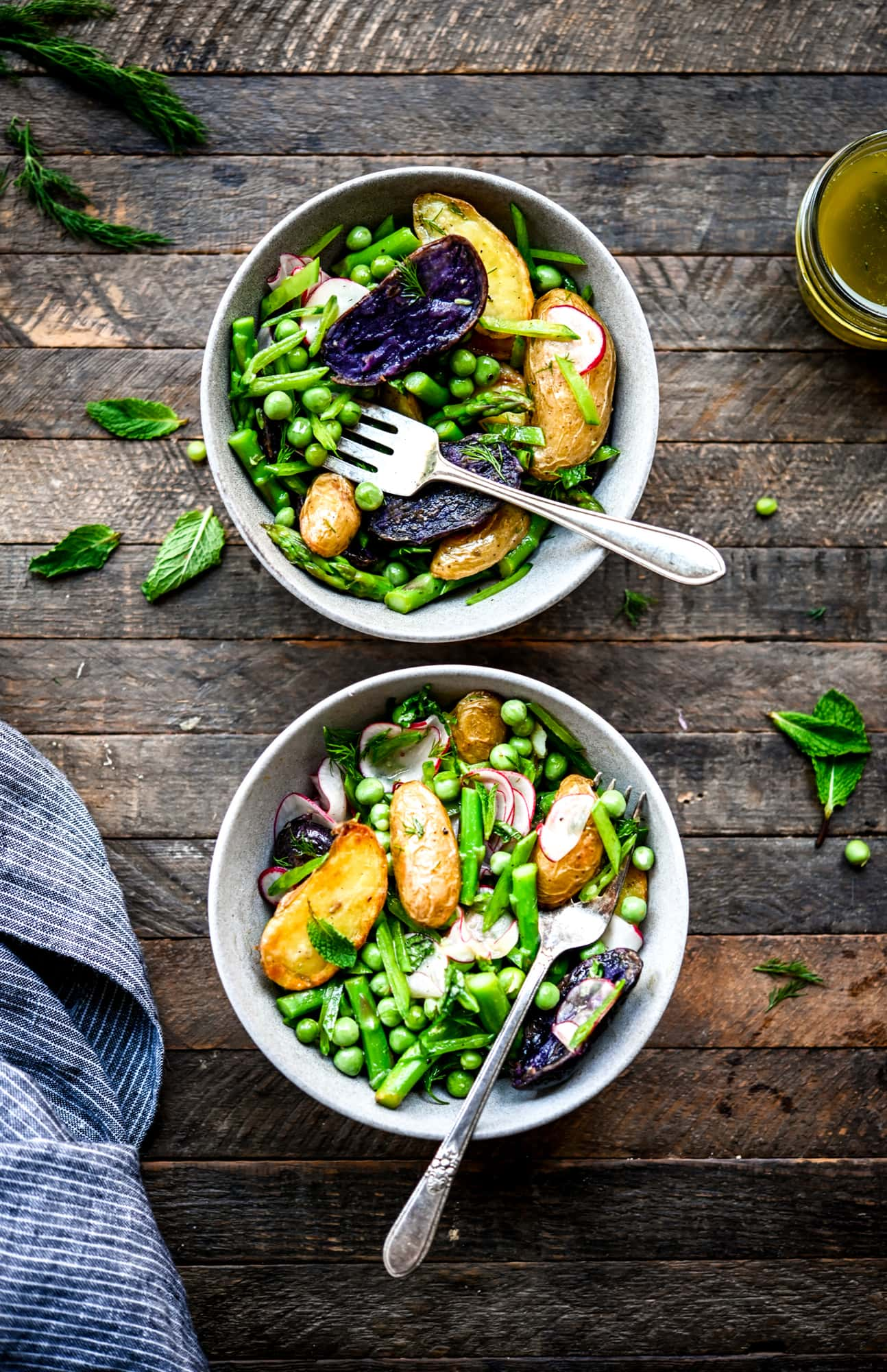 overhead view of two bowls of spring potato salad with asparagus