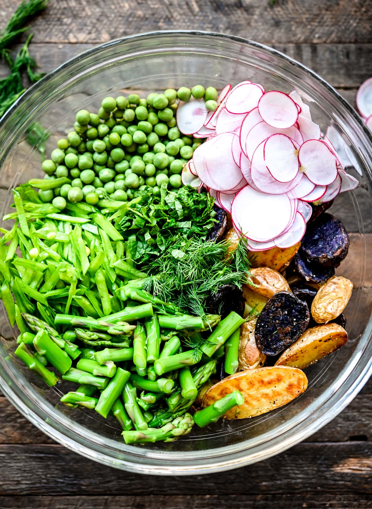 Overhead view of ingredients for spring potato salad in a glass bowl