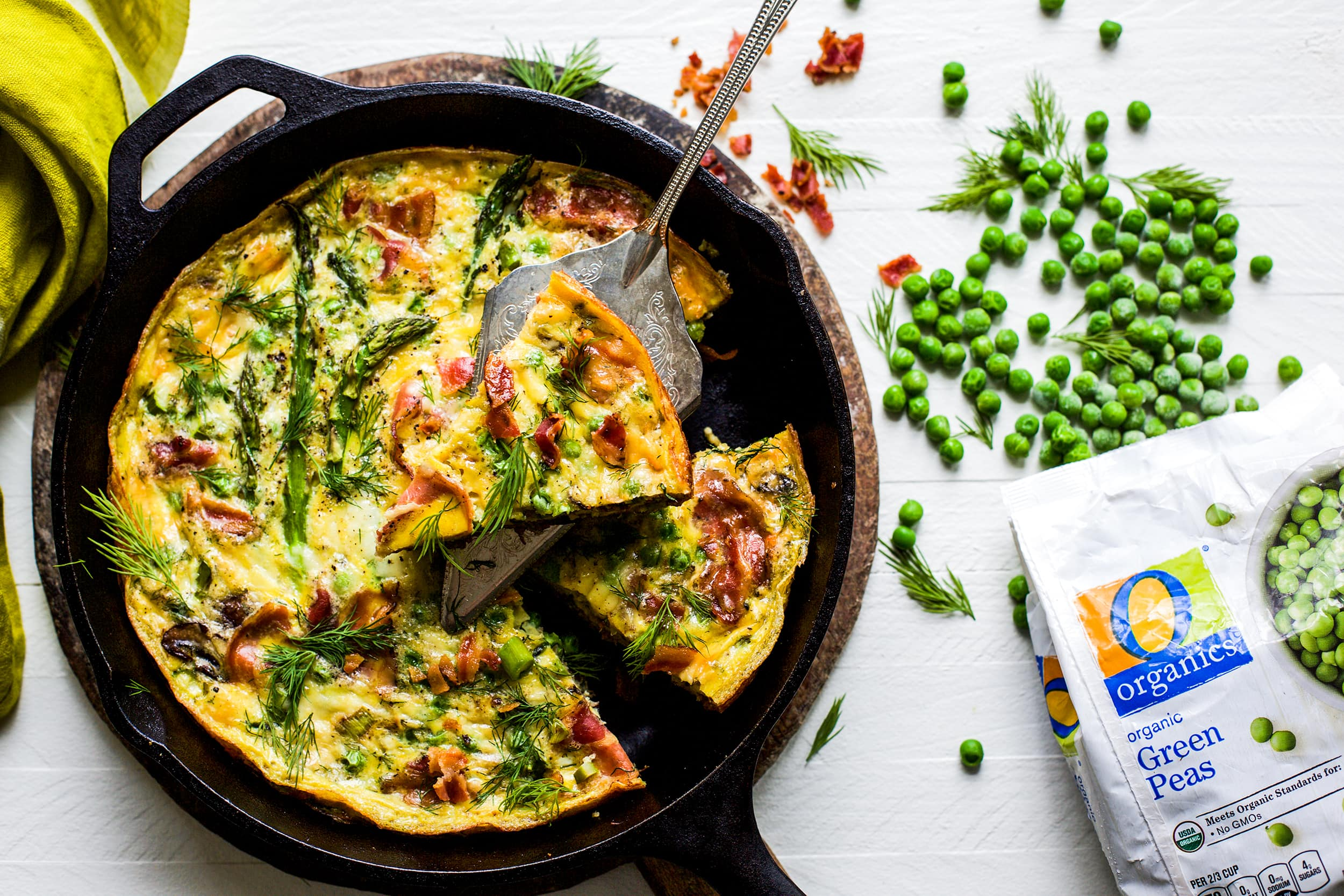 Overhead view of spring frittata in a cast iron skillet on white background
