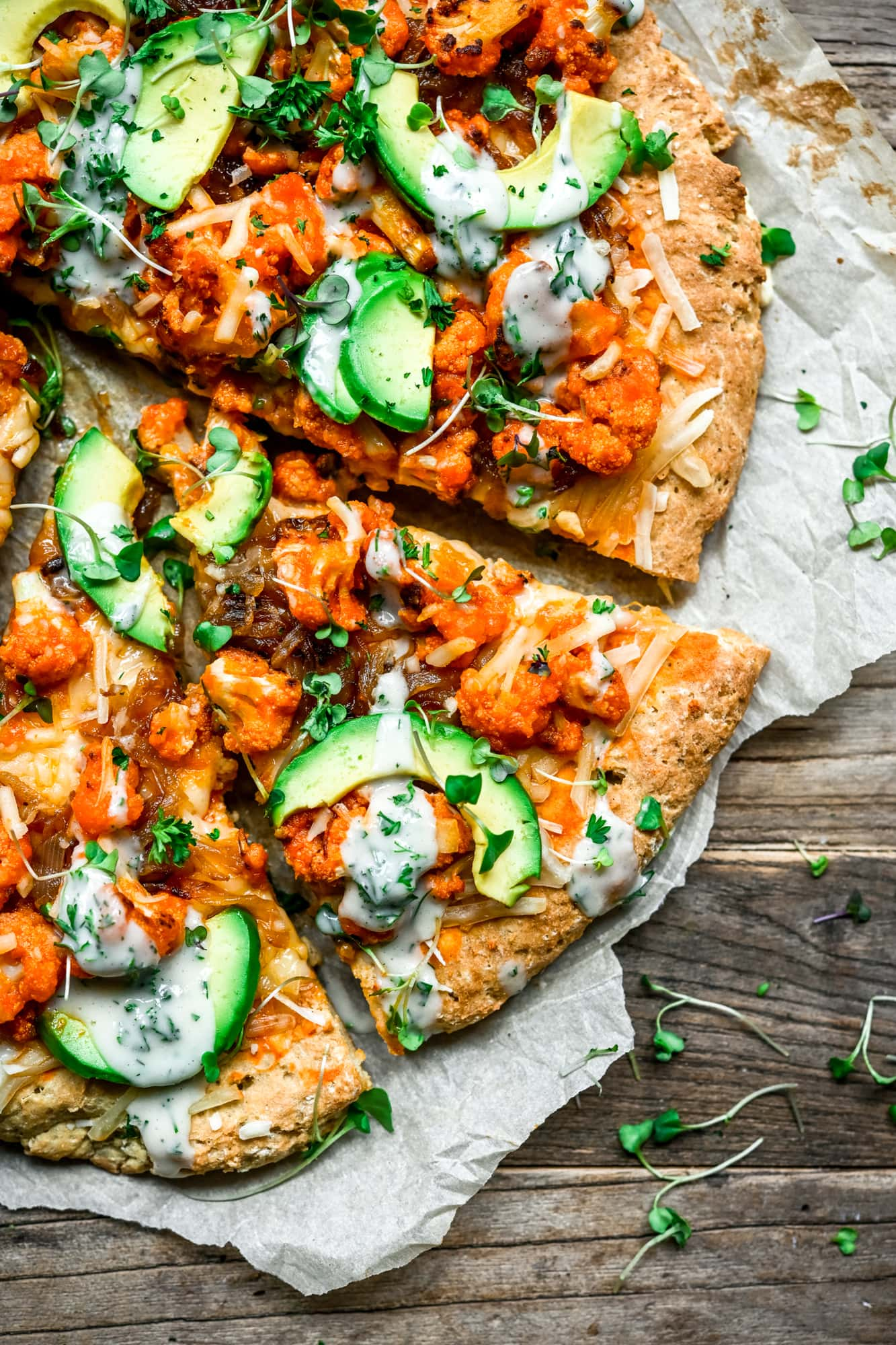 Overhead view of vegan comfort food buffalo cauliflower pizza with avocado slices and ranch drizzle on parchment paper