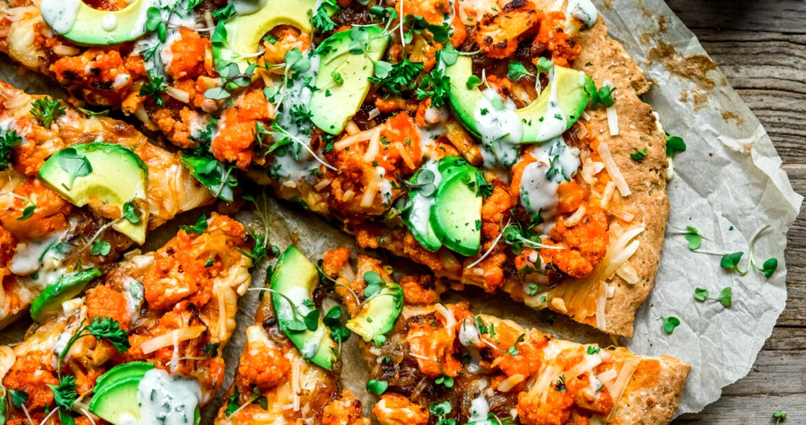 Overhead view of sliced vegan buffalo cauliflower pizza with avocado slices and ranch drizzle on parchment paper