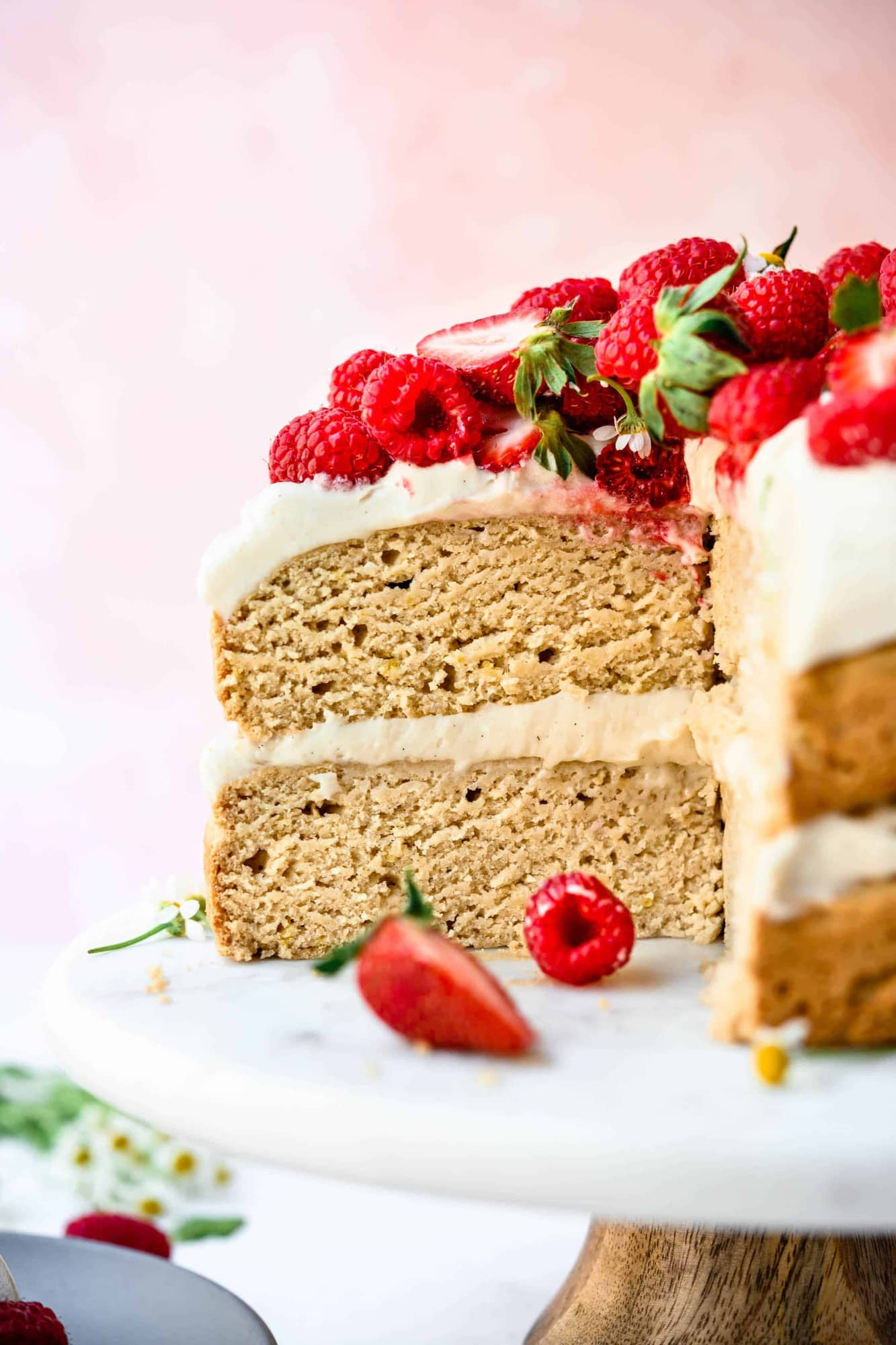 Side view of slice of vegan and gluten free layer cake topped with fresh berries