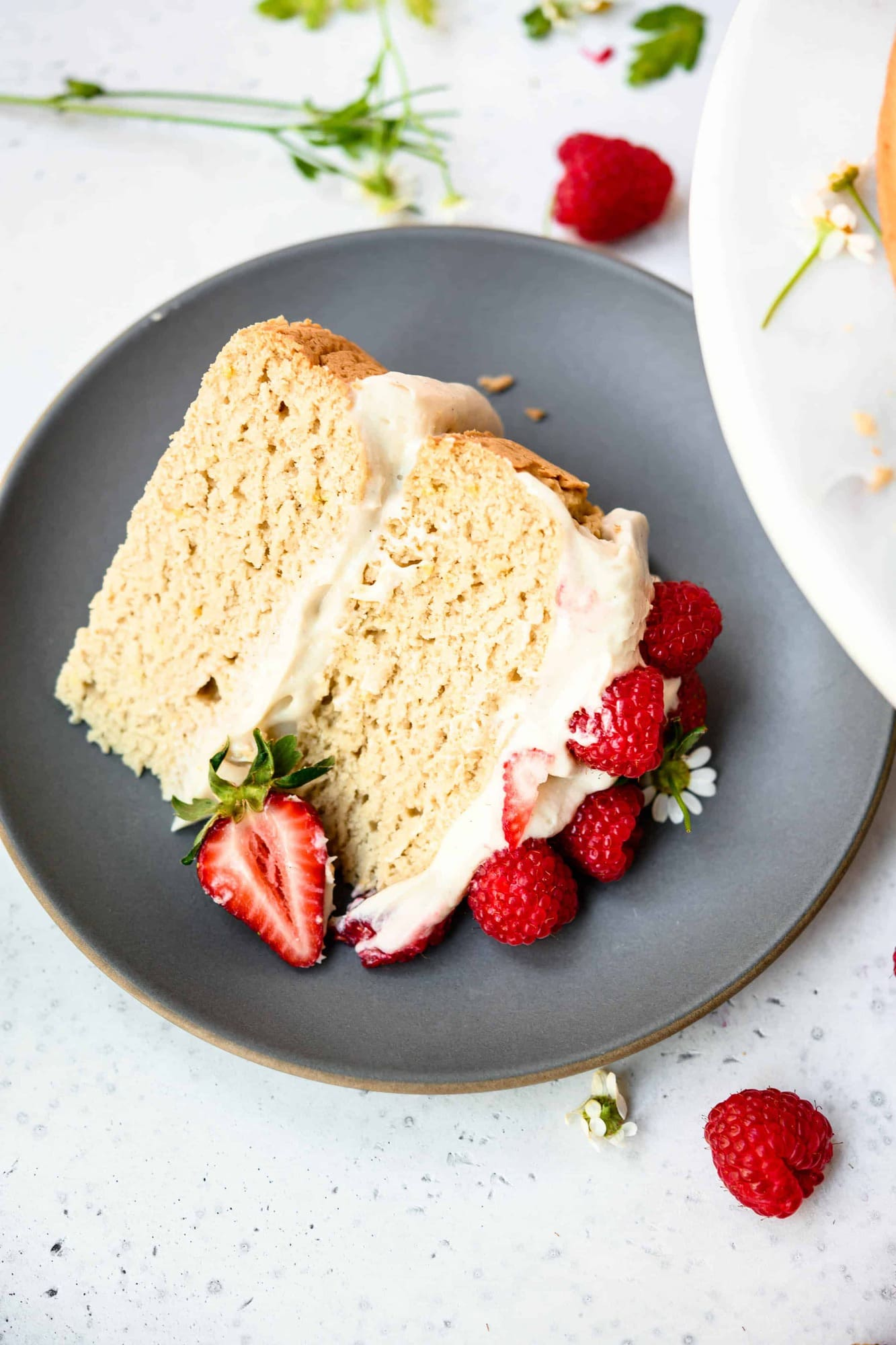 High side view of slice of vanilla layer cake topped with fresh berries on a gray plate