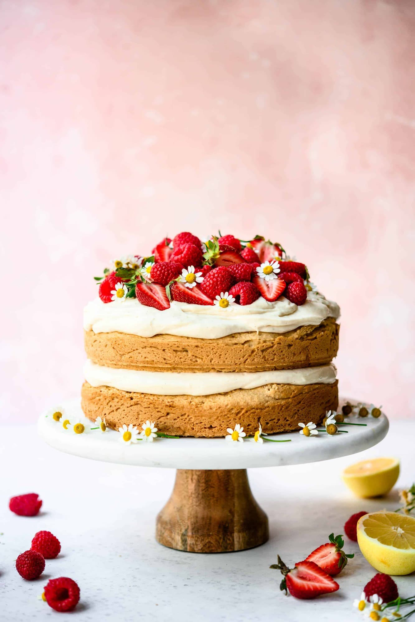 Side view of lemon almond layer cake topped with fresh berries on marble cake stand