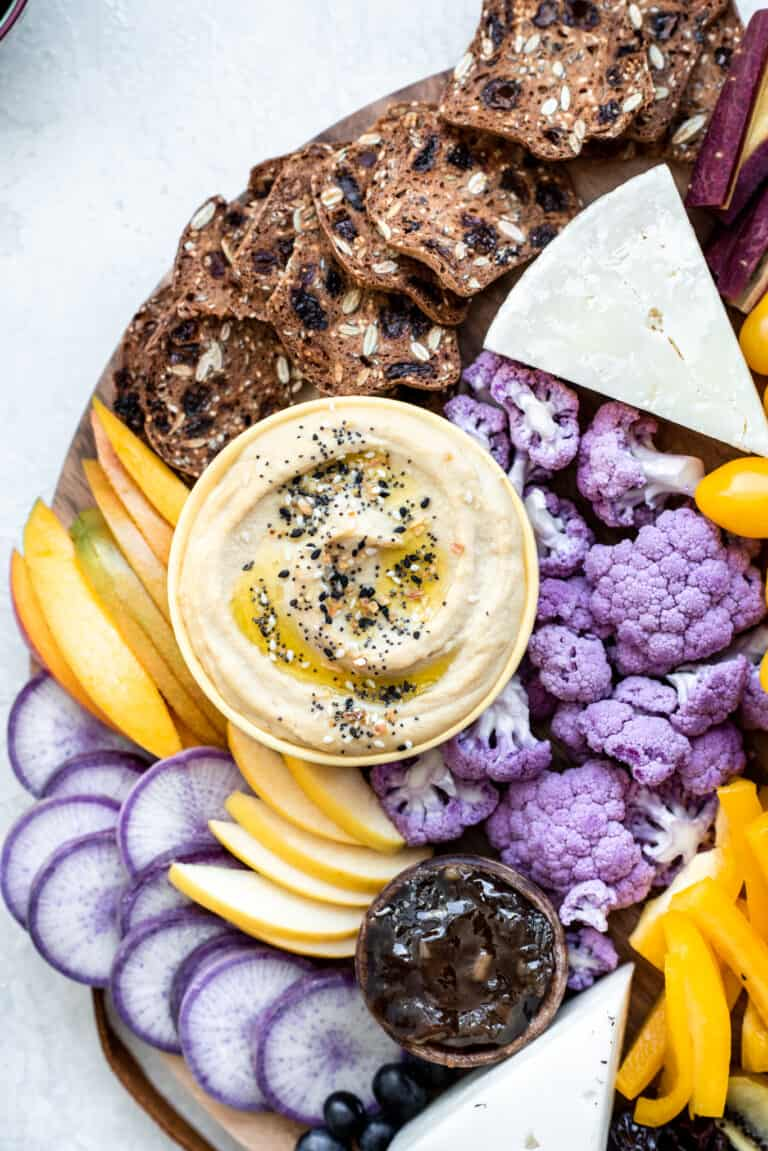 Close up Overhead view of purple and yellow hummus appetizer platter on a gray background
