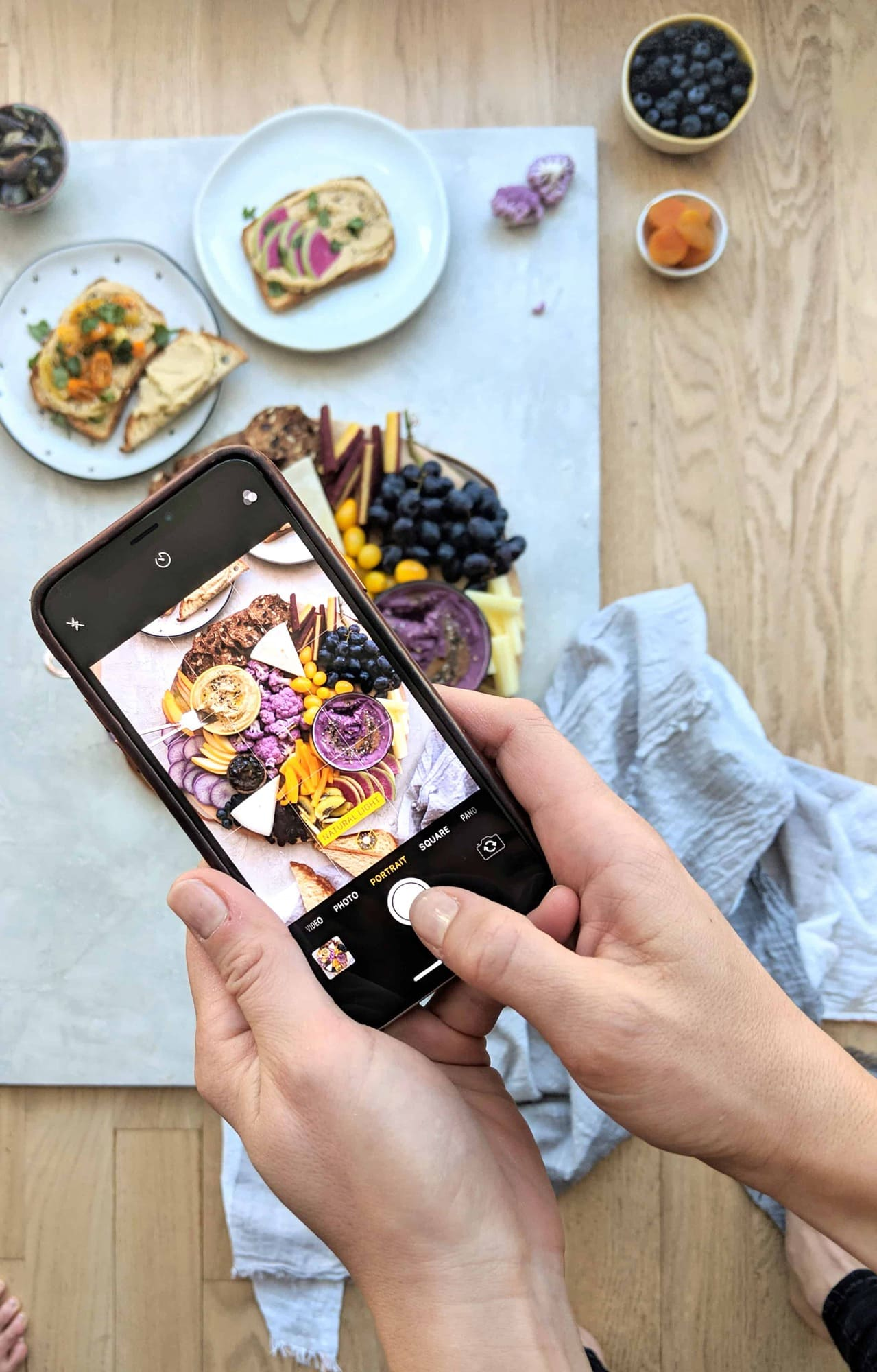 Photo of an iphone taking a photo of a yellow and purple hummus appetizer platter