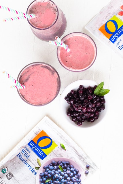 Overhead view of three blueberry smoothies next to a bowl of frozen blueberries