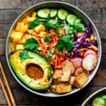 Overhead view of vegan spring roll bowl with crispy tofu and avocado on wood background