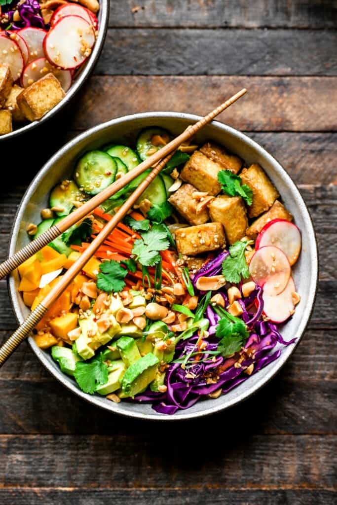 Overhead view of bowl with crispy tofu and rice noodles and sesame miso dressing for meal prep