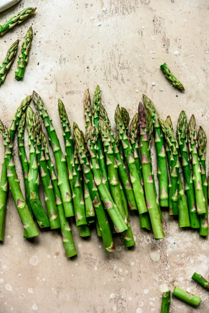 Overhead view of beautiful food photography of asparagus spears on a light tan background