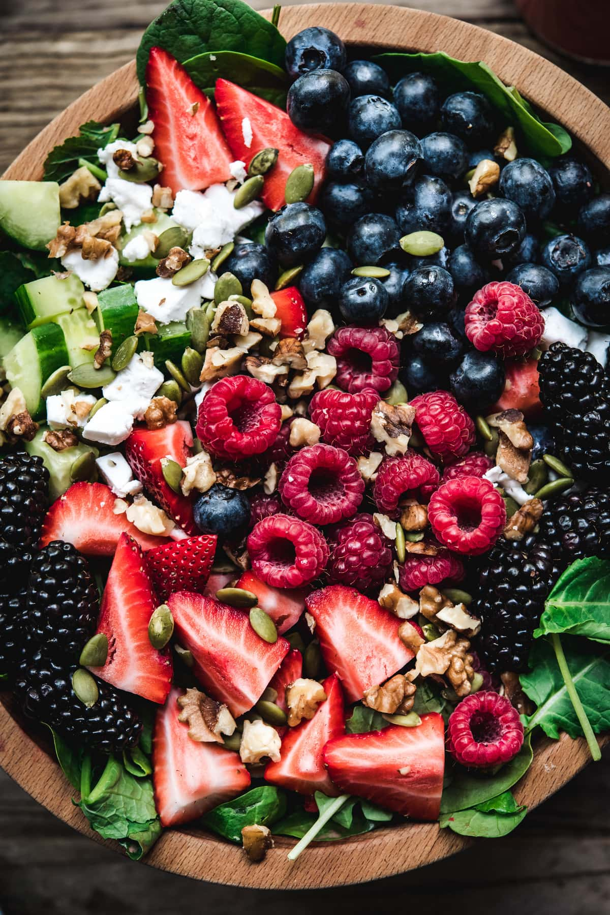 Close up Overhead view of berry spinach salad with feta and cucumbers in wooden bowl