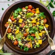 Black bean and mango salad in a wooden bowl with a fork and a spoon to toss.