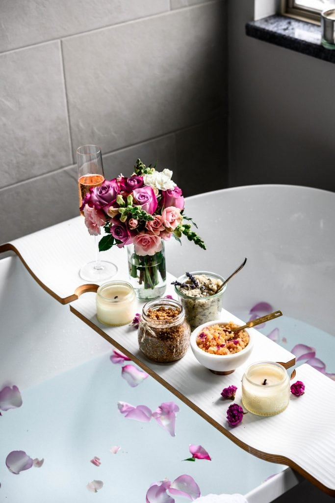 Side view of relaxing bath tub with body scrubs, champagne, flowers and candles