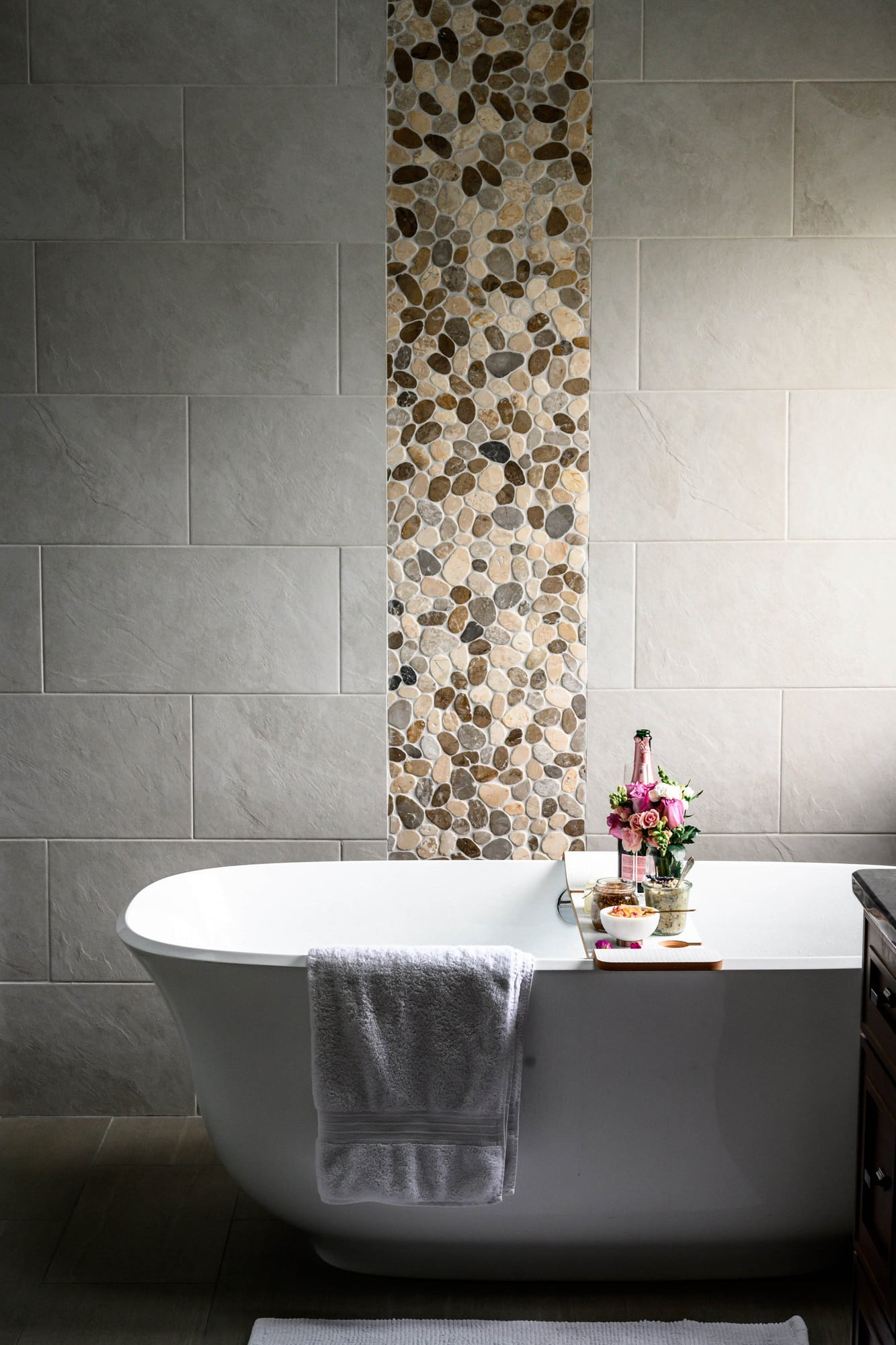 Side view of relaxing, beautiful bath tub with body scrubs, champagne, flowers and candles