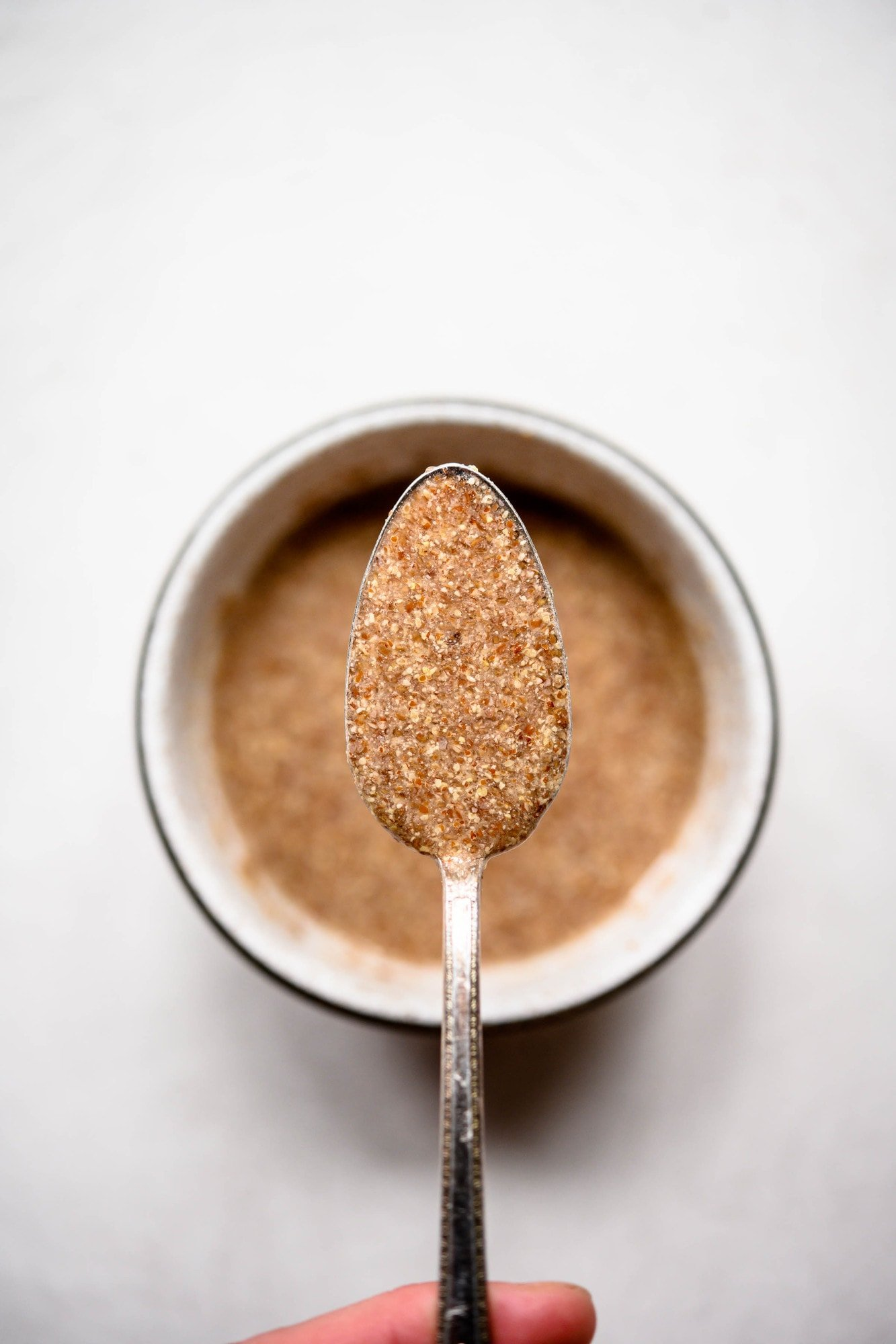 Close up of person holding spoon of flax egg over bowl on white background