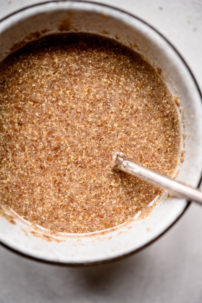 Overhead view of water and flax meal in bowl to make a vegan flax egg