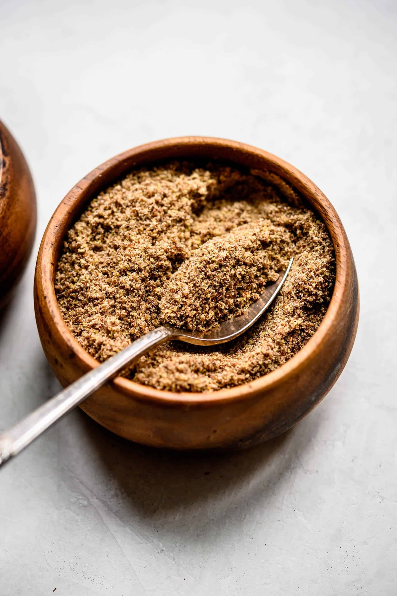 Close up side view of flax meal in a small wooden bowl