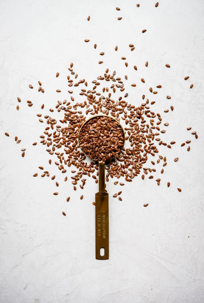 Overhead view of flax seeds on and around a gold measuring spoon on white background