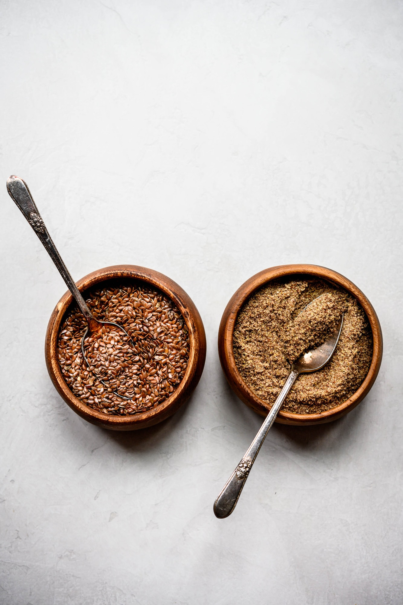 Overhead flax seed and flax meal in two small wooden bowls on white background